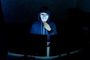 Masked hacker under hood using compu