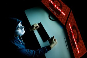 Masked hacker under hood using compu