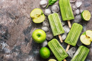 Green popsicles on a wooden