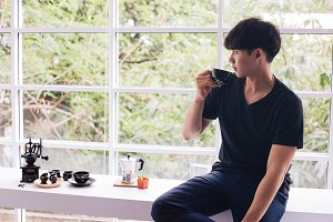 Asian young man drinking coffee insi