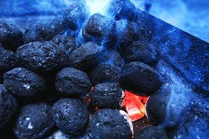 Hot flaming charcoal briquettes glow