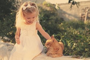 little girl stroking a red cat