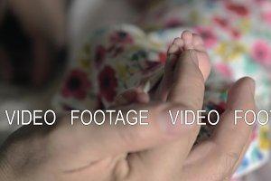 Grandpa touching baby feet
