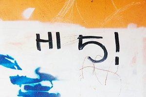 Graffiti tag hi 5 on grungy wall
