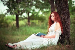 Red-haired woman sitting under tree