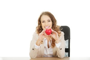 Business woman holding red heart.