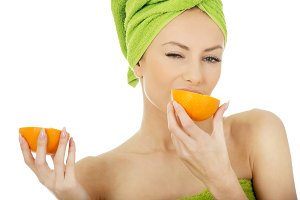 Beautiful woman eating orange.