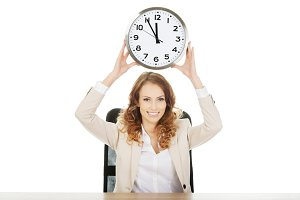 Businesswoman with clock by a desk.