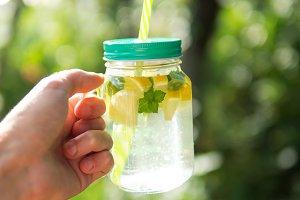 Glass jar with lemonade in hand