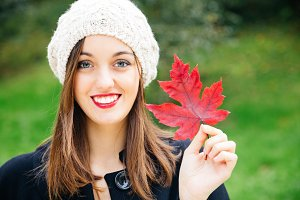 Beautiful woman holding an autumn le