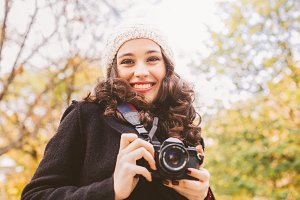 Cute photographer woman in autumn
