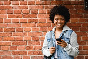 Happy hipster girl looking at phone