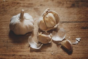 raw garlic on a wooden plank and ton