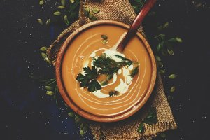 Creamy pumpkin soup in a wooden bowl