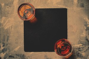 Cognac in two glasses on stone backg