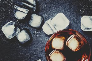 Cold whiskey with ice, black backgro