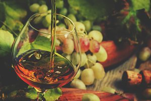 Cognac Pour In Glass, Grapes And Vin