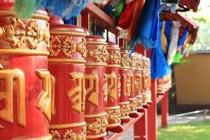Prayer drums row. Buddhist temple.