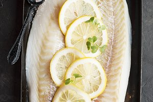 Raw cod fillets with lemon slices on