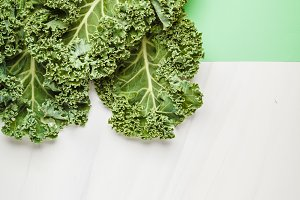 Leaves of kale on green background