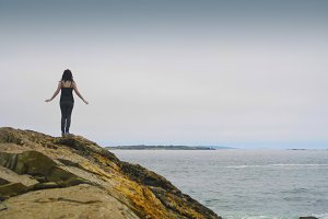 Woman on rocky cliff, arms out