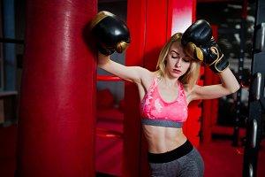 Sexy sport blonde girl punching bag.
