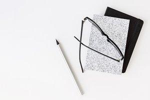 Notebooks and eyeglasses on desk