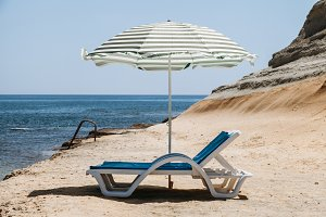 Two blue deck chairs with a beach um