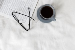 Coffee cup, eyeglasses and magazine