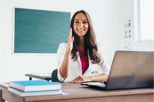 Girl raises hand sitting at the desk