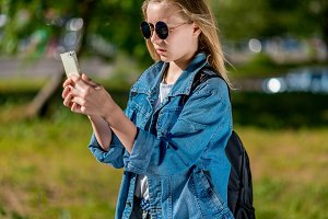 Girl schoolgirl in summer in park