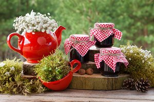 Red teapot, tea cup and jars of jam