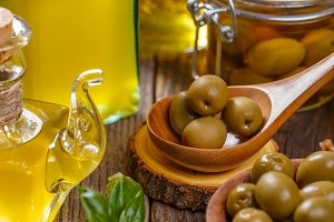 Olive oil in glass bottle and olives