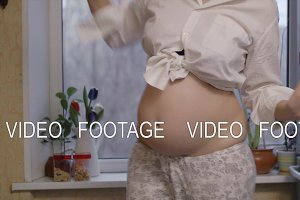 Cheerful pregnant woman dancing at