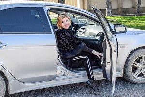 The girl opens the door in the car