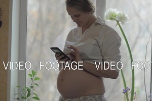 Smiling pregnant woman with mobile