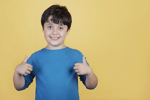 Little boy smiling showing thumbs up