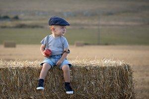little boy sitting on a haystack