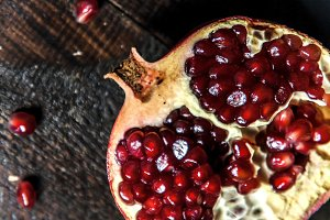broken pomegranate close-up on a dar