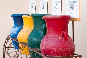 Colorful clay pots in a trash can at