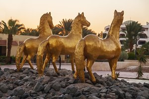 three gold statue of a horse on a ba