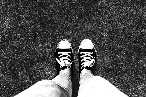 Legs in old sneakers on grass. View