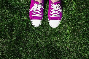 Legs in old pink sneakers on green g