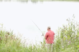 Mature angler catching fish on lake