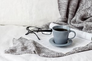 Coffee cup with gray blanket on bed