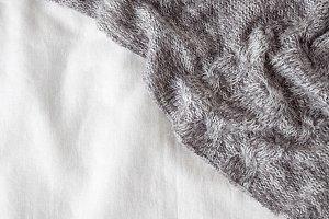 Gray blanket on white linen bedding