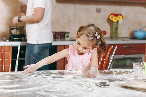 Little kid girl play with flour whil