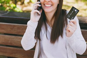 Female holding credit card, talking