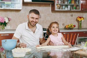 Little kid girl helps man to cook la