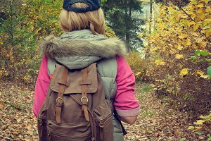 Tourist with backpack in autumn fore
